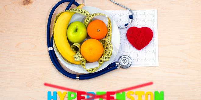 A bowl of fruit, measuring tape, and a stethoscope on a cardiac chart