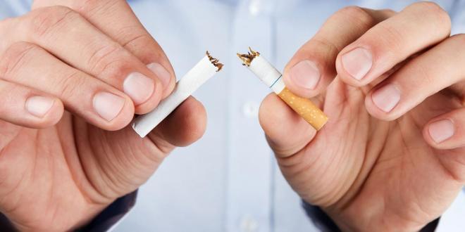 A man breaking a cigarette in half